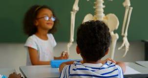 Vista frontale della scolara afroamericana che spiega modello di scheletro in aula alla scuola 4k stock footage
