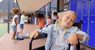 Vista frontale della scolara caucasica disabile che sorride nel corridoio 4k stock footage