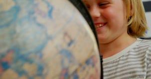 Vista frontale della scolara caucasica felice che studia globo allo scrittorio in aula alla scuola 4k video d archivio