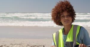 Vista frontale della spiaggia di pulizia volontaria femminile afroamericana un giorno soleggiato 4k stock footage