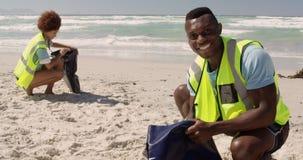 Vista frontale della spiaggia di pulizia volontaria maschio afroamericana un giorno soleggiato 4k video d archivio