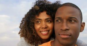 Vista frontale delle coppie afroamericane che si abbracciano sulla spiaggia 4k video d archivio