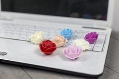 Vista frontale delle rose colourful e del computer portatile bianco su fondo di legno grigio immagine stock