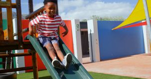 Vista frontale dello scolaro afroamericano che gioca sugli scorrevoli nel campo da giuoco 4k della scuola video d archivio