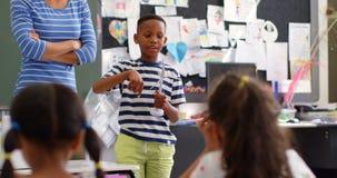 Vista frontale dello scolaro afroamericano che spiega circa il modello del mulino a vento nell'aula 4k stock footage