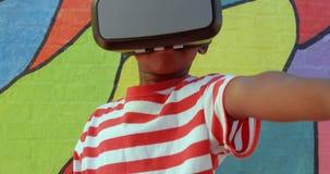Vista frontale dello scolaro afroamericano che utilizza la cuffia avricolare di realtà virtuale contro la parete nella scuola 4k video d archivio