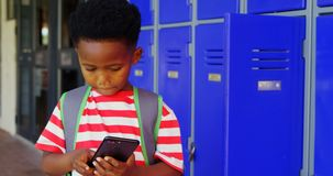 Vista frontale dello scolaro afroamericano con la cartella facendo uso del telefono cellulare in corridoio 4k della scuola video d archivio