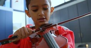 Vista frontale dello scolaro asiatico attento che gioca violino in aula alla scuola 4k video d archivio