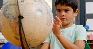 Vista frontale dello scolaro caucasico che studia globo allo scrittorio in aula alla scuola 4k archivi video