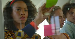Vista frontale di giovane dirigente femminile afroamericano che lavora alle note appiccicose in ufficio moderno 4k archivi video