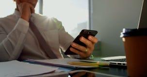 Vista frontale di giovane dirigente maschio caucasico che lavora al telefono cellulare allo scrittorio in ufficio moderno 4k video d archivio