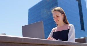 Vista frontale di giovane donna di affari caucasica fresca che lavora al computer portatile in balcone dell'ufficio moderno 4k video d archivio