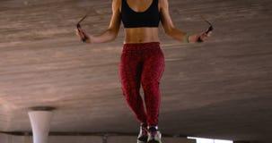 Vista frontale di giovane donna afroamericana che si esercita con il salto della corda nella città 4k archivi video