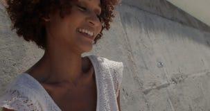 Vista frontale di giovane donna afroamericana che si rilassa sulla spiaggia nel sole 4k video d archivio