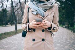 Vista frontale di giovane donna alla moda che porta cappotto beige immagine stock
