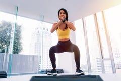 Vista frontale di giovane donna asiatica attraente di forma fisica in abiti sportivi che fanno edificio occupato profondo alla pa fotografie stock libere da diritti