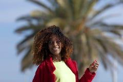 Vista frontale di giovane donna riccia sorridente di afro che sta all'aperto mentre sorridendo e distogliendo lo sguardo in un gi fotografia stock libera da diritti