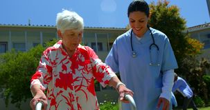 Vista frontale di medico femminile caucasico che aiuta paziente senior a camminare con il camminatore nel giardino del NU stock footage