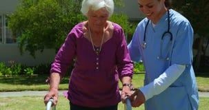 Vista frontale di medico femminile caucasico che aiuta paziente senior a camminare con il camminatore nel giardino del NU video d archivio