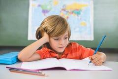 Vista frontale di scrittura del ragazzo sul libro in aula Immagini Stock