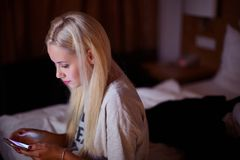 Vista frontale di un telefono di controllo teenager triste che si siede sul pavimento nel salone a casa con un fondo scuro fotografia stock