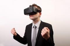 Vista frontale di un uomo che indossa una cuffia avricolare della spaccatura 3D dell'occhio di realtà virtuale di VR, in un comba Fotografia Stock