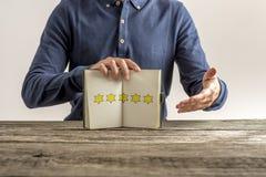 Vista frontale di un uomo che presenta un blocco note aperto con cinque dorati Fotografia Stock