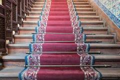 Vista frontale di vecchie scale di legno salenti con tappeto rosso decorato Fotografie Stock