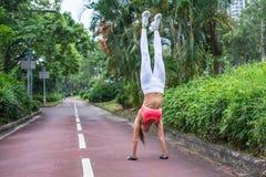 Vista frontale di yoga di pratica della giovane donna esile di misura che fa verticale diritto il giorno di estate del percorso d Fotografia Stock