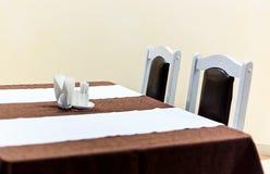 Vista genérica de la tabla del restaurante con la tabla cubierta por las servilletas del anf del mantel en ella Imagen de archivo libre de regalías