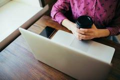 Vista geral de uma mulher na frente do portátil com uma xícara de café fotos de stock royalty free