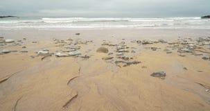 Vista geral de uma praia com os grandes formulários feitos por córregos na areia fina filme