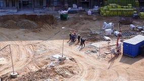 Vista geral do canteiro de obras de uma área residencial na cidade - uma equipe dos construtores discute o próximo trabalho video estoque