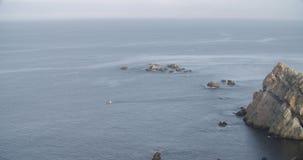Vista geral do mar com um barco que cruza o com uma formação de rochas video estoque