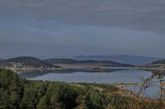 Vista geral do reservatório da represa de Batak, da clareira litoral do outono, da floresta com reflexão e dos montes em montanha imagens de stock
