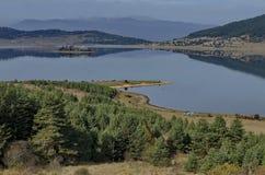 Vista geral do reservatório da represa de Batak, da clareira litoral do outono, da floresta com reflexão e dos montes em montanha imagem de stock royalty free