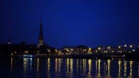 Vista geral em Riga através do rio do Daugava na noite filme