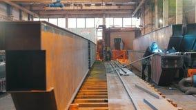 Vista geral lisa de estruturas do metal no território da fábrica s Um soldador aparece no quadro vídeos de arquivo