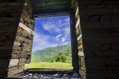 Vista gloriosa del valle de Janjheli a través de una ventana enmarcada de madera Fotografía de archivo