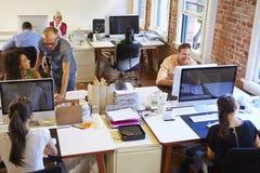 Vista granangular de la oficina conceptora ocupada con los trabajadores en los escritorios imágenes de archivo libres de regalías