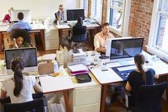 Vista grandangolare dell'ufficio progetti occupato con i lavoratori agli scrittori immagini stock