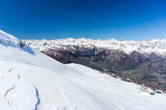 Vista grandangolare di una stazione sciistica nella distanza con i picchi di montagna eleganti in seguito all'arco alpino nella s Fotografia Stock Libera da Diritti