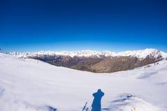 Vista grandangolare di una stazione sciistica nella distanza con i picchi di montagna eleganti in seguito all'arco alpino nella s Immagini Stock
