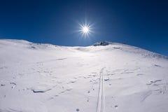 Vista grandangolare di una stazione sciistica nella distanza con i picchi di montagna eleganti in seguito all'arco alpino nella s Immagini Stock Libere da Diritti