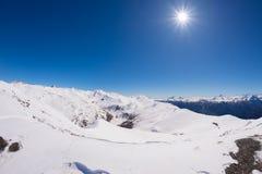 Vista grandangolare di una stazione sciistica nella distanza con i picchi di montagna eleganti in seguito all'arco alpino nella s Fotografie Stock Libere da Diritti