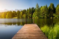 Vista idilliaca del pilastro di legno nel lago con il fondo di paesaggio della montagna Fotografie Stock