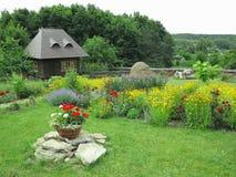 Vista idilliaca della casetta su un fondo dei fiori e del verde fotografia stock