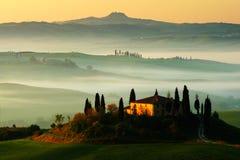 Vista idilliaca di terreno coltivabile collinoso in Toscana alla bella luce di mattina, Italia Paesaggio nebbioso in Toscana Belv Fotografie Stock