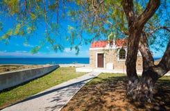 Vista ilustrada asombrosa de una iglesia de piedra vieja al lado del mar azul, Milatos, Creta Imagenes de archivo