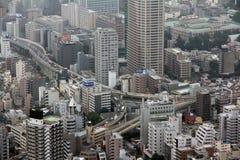 Vista industrial do Tóquio com estradas e os arranha-céus ocupados Imagem de Stock